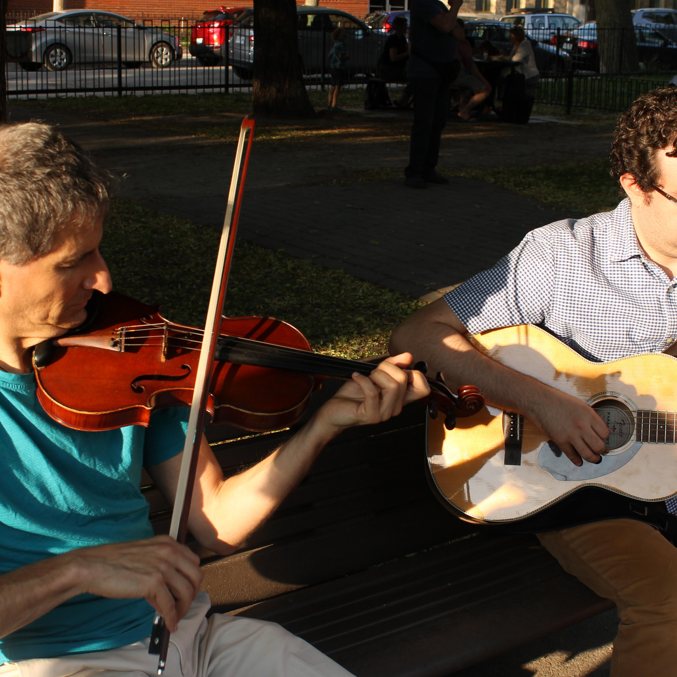 Two musicians playinf on a parc bench